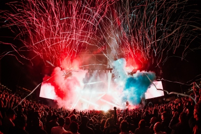 Stage at a festival with red and blue smoke and lights